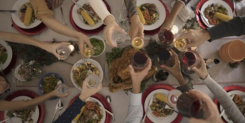 Overhead view family toasting wine glasses at candlelight Christmas turkey dinner at table