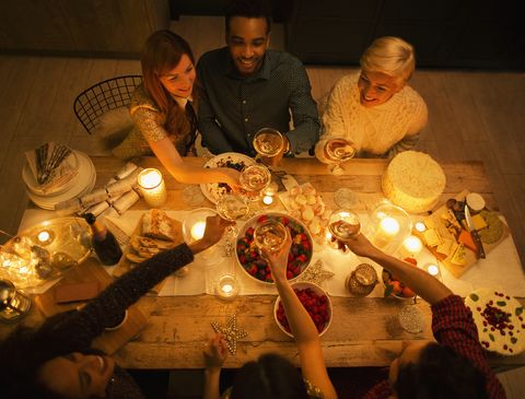 Overhead view friends toasting champagne glasses at candlelight Christmas dessert