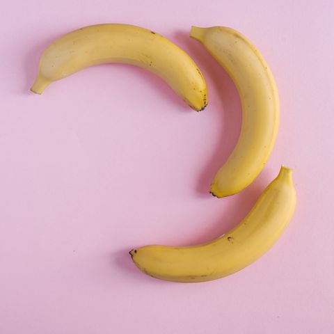 Overhead view of bananas on pink background