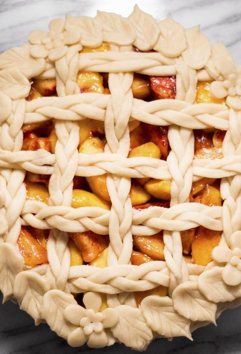 Overhead view of floral peach pie on marble counter