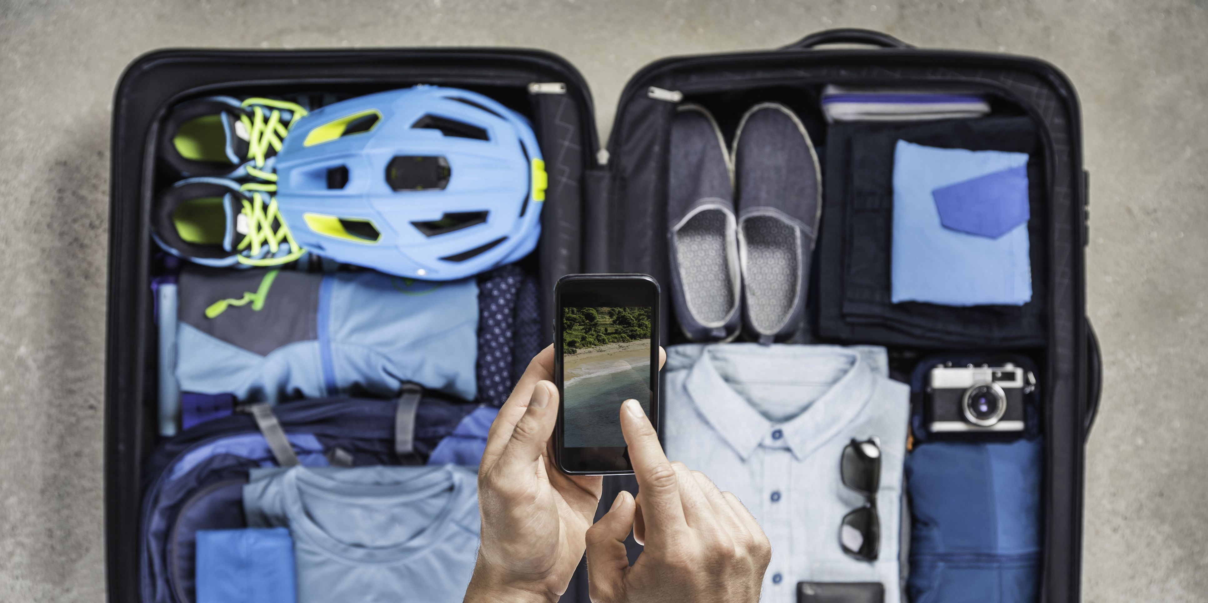 Overhead view of mans hands using smartphone touchscreen above packed suitcase with blue bike helmet, backpack, retro camera and shirt
