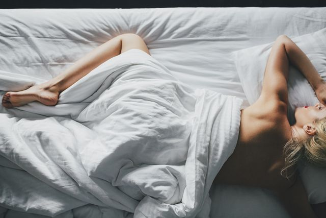 overhead view of sensuous woman lying on bed at home