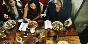Overhead view of smiling female friends sharing lunch in restaurant