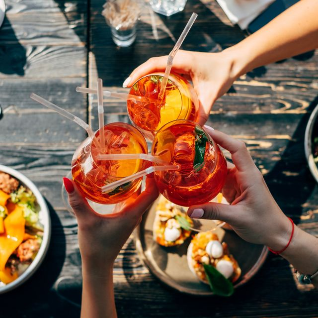 overhead view of three women making a celebratory toast with spritz cocktails