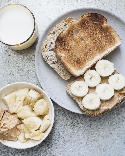 overhead view of toast with peanut butter, banana and milk