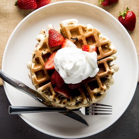 Overhead view of waffles garnished with strawberries and whipped cream