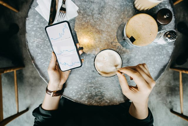 overhead view of woman checking financial trading data on smartphone while drinking coffee in cafe