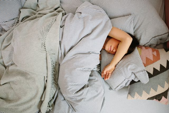 sleep talking woman lying in bed sleeping