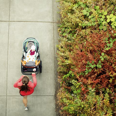 overhead view of woman running while holding baby stroller in park