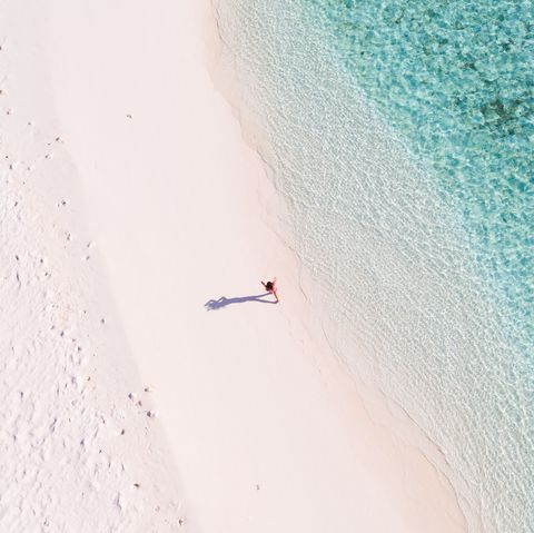 Overhead view of woman walking on a beach, Maldives
