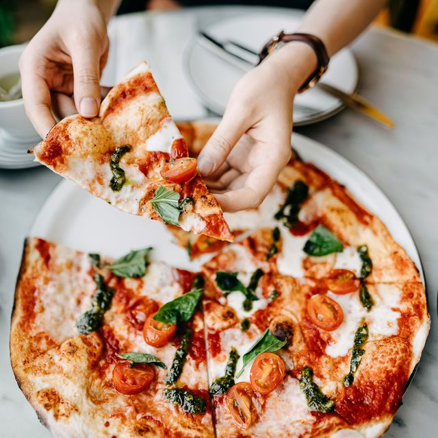 overhead view of woman's hand getting a slice of freshly made pizza and enjoying her meal in an italian restaurant