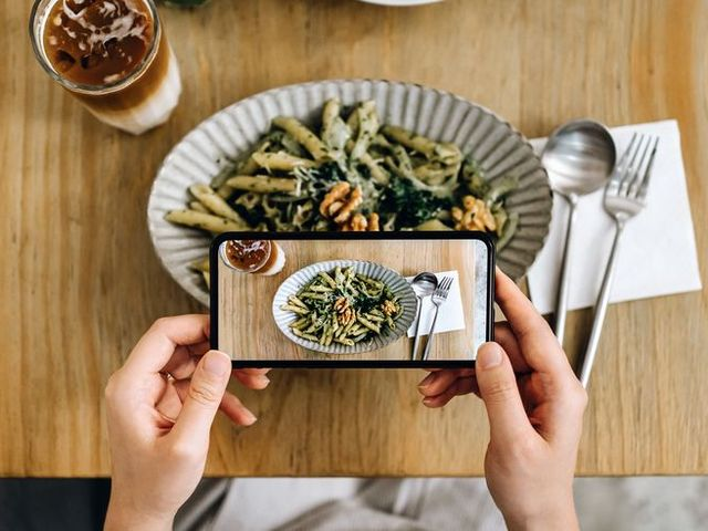 overhead view of woman's hand taking a photo of freshly served food with smartphone while having meal with friend in a restaurant