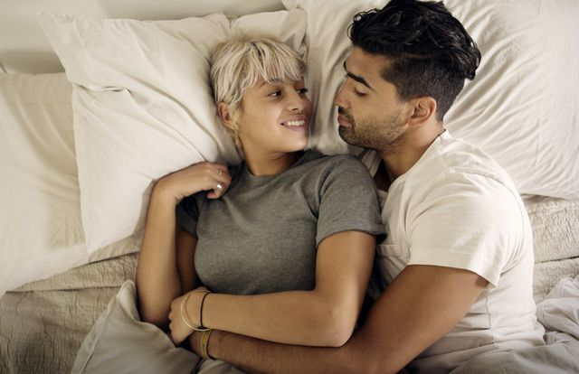 overhead view of young couple relaxing on bed at home
