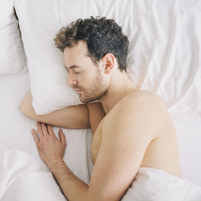 overhead view of young man lying asleep in bed