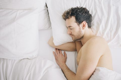 Top view of young man lying asleep in bed
