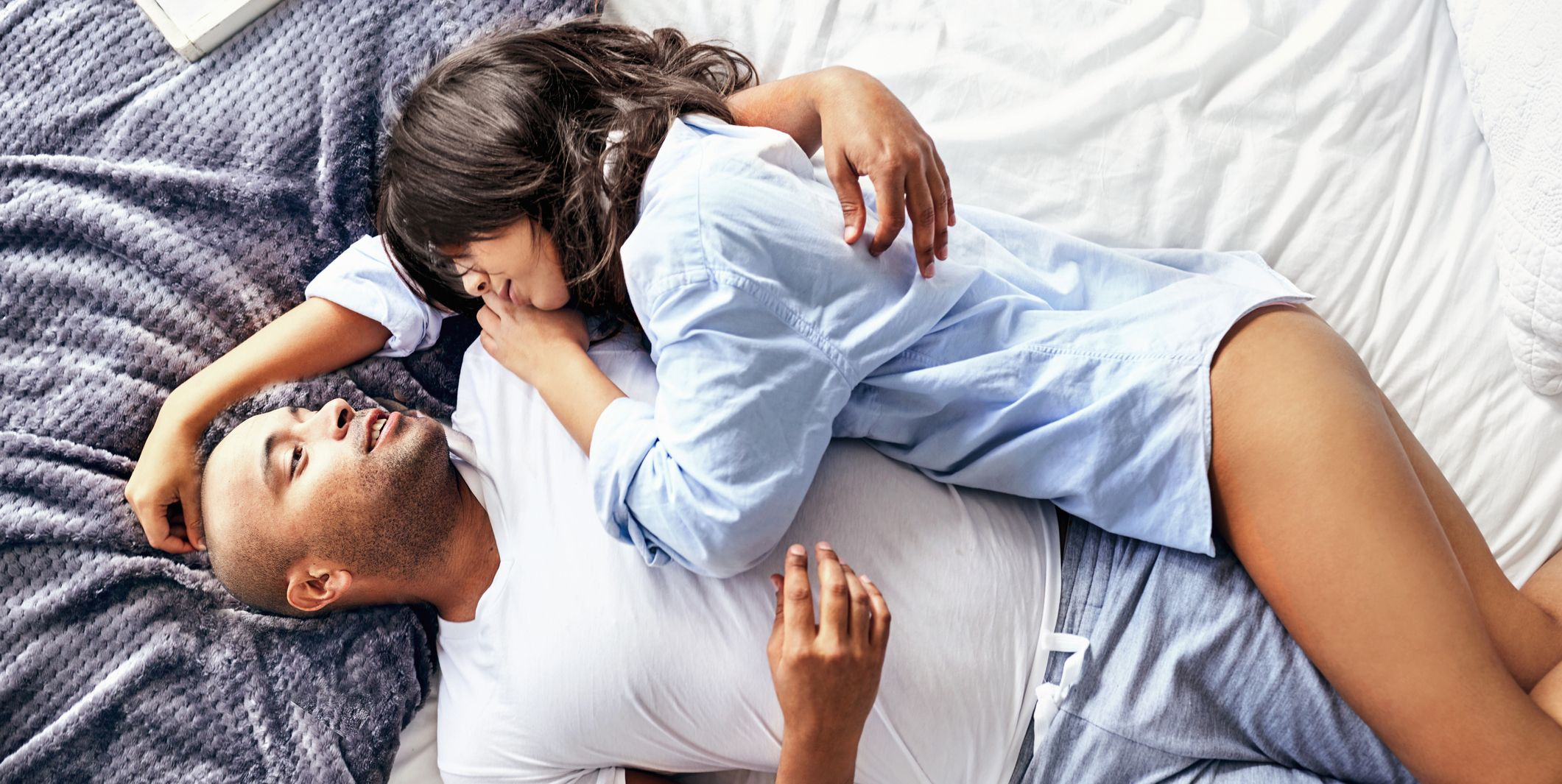 Overhead view sensual couple in pajamas cuddling on bed