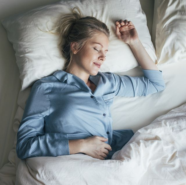sound asleep overhead waist up shot of a pretty blonde woman in blue pyjamas sleeping on a king size bed