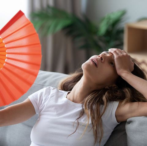 overheated woman sitting on couch, waving fan, feeling unwell