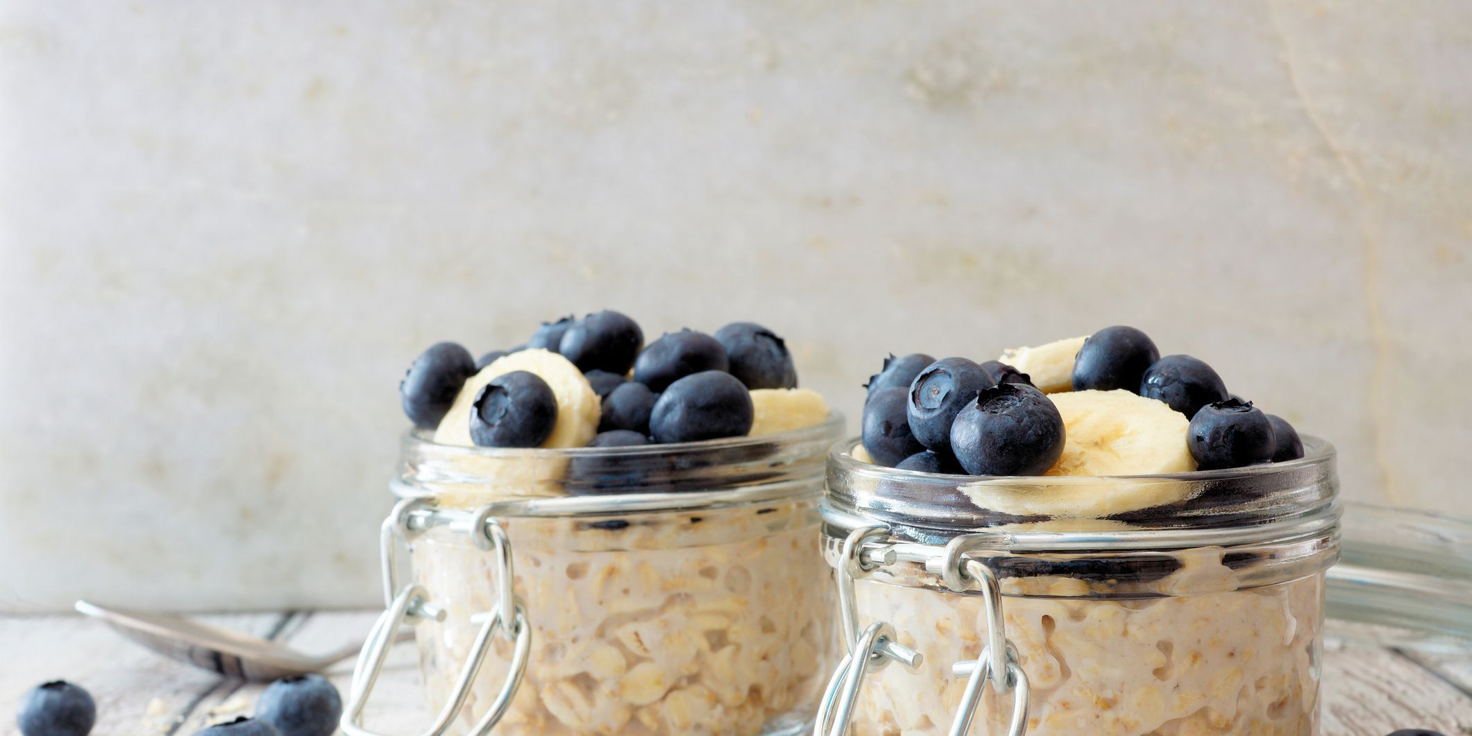 Overnight oats with blueberries and bananas on a white wood background