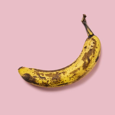 overripe banana on pink background