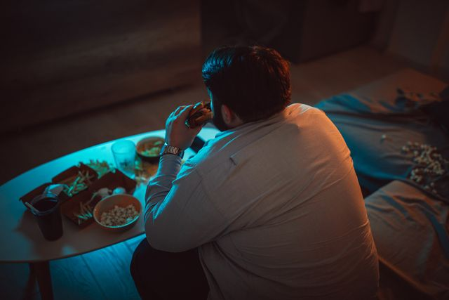 overweight man eating a burger