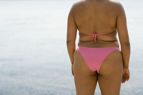 overweight woman in bikini at beach, midsection