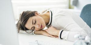 Overworked woman sleeping on desk in office