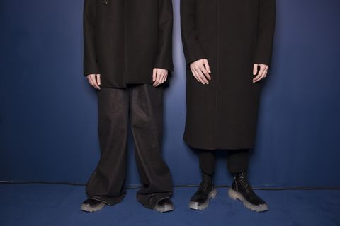 Standing, Outerwear, Formal wear, Hand, Uniform, Suit, Gesture, Trousers, Coat,