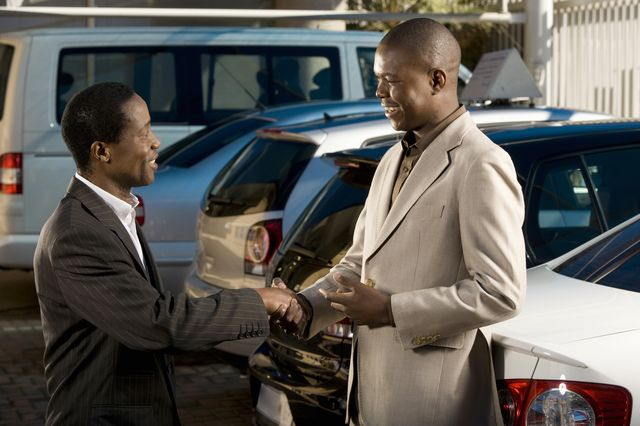 owners of car dealership shaking hands, johannesburg, south africa