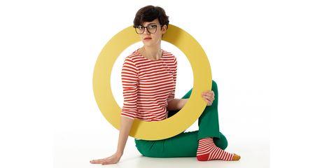 Green, Sitting, Leg, Textile, Neck, Furniture, Bean bag, Costume, Stomach,