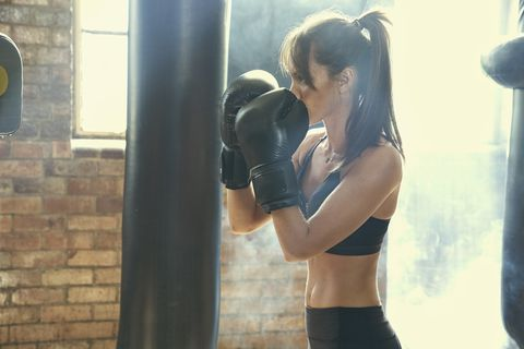 pacific islander woman hitting punching bag in gymnasium
