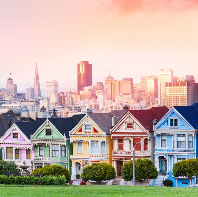 early evening warm light skyline of san francisco and painted ladies from alamo park square