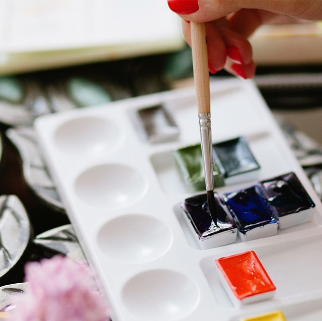 woman dipping paintbrush into paint on palette