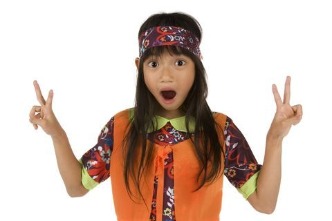 little girl dressed as hippie for halloween giving peace sign hand gestures