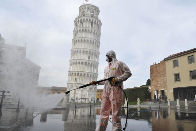 pisa, italy   march 17  a worker carries out sanitation operations for the coronavirus emergency in piazza dei miracoli near to the tower of pisa in a deserted town on march 17, 2020 in pisa, italy the sanitization service is carried out by four teams in all the districts of the city of pisa, to sanitize the squares, streets, public areas, sidewalks, surfaces exposed to the contact of large flows of people italian government has imposed unprecedented restrictions on its 60 million people as it expanded its emergency coronavirus covid 19 lockdown nationwide the number of confirmed covid 19 cases in italy has passed 31,500 with the death toll rising to 2503  photo by laura lezzagetty images