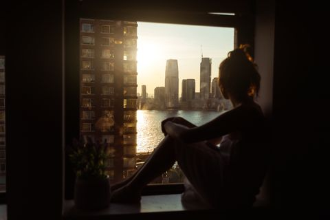 pandemic covid 19 lockdown pensive woman home at the window over new york city manhattan