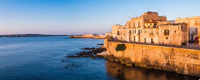 panoramic photo of ortigia old city at sunrise, with ortigia castle, castello maniace, castle maniace, in the background, syracuse, siracusa, unesco world heritage site, sicily, italy, europe