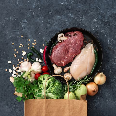 Paper bag food with vegetables, fruit and meat on dark background with copy space top view