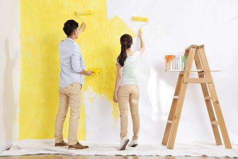 pareja pintando la pared de color amarillo
