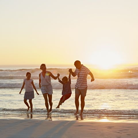Parents with children enjoying vacation on beach