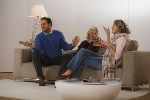 parents with daughter sitting on sofa in living room