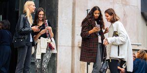 Modellen op straat in Parijs met hun telefoon