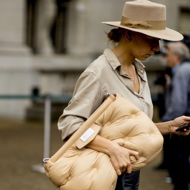 Street fashion, Hat, Snapshot, Sitting, Fashion, Fedora, Headgear, Outerwear, Leg, Beige,