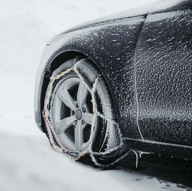 parking car in the snow with snow chains in front of a wood cabin