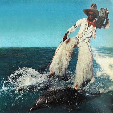 man carrying a boombox wearing furry chaps water skiing on two dolphins