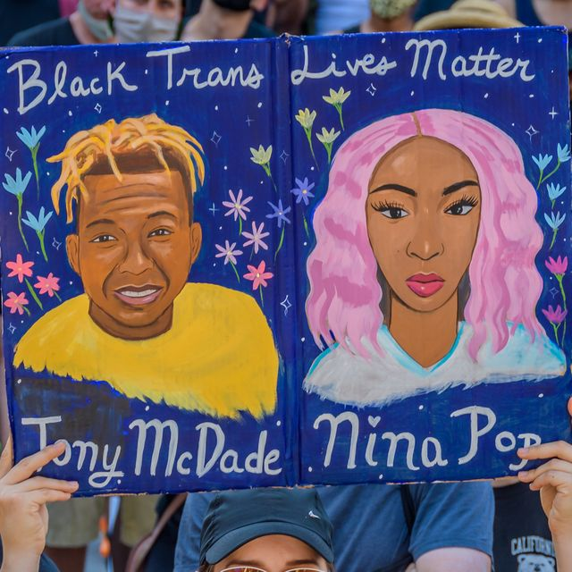 a participant holding a black trans lives matter sign at the