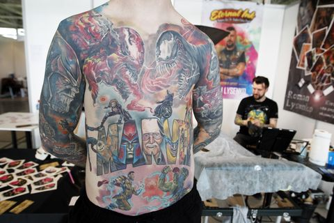 a participant is seen showing off his tattooed body during