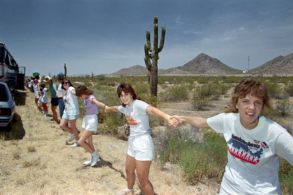 Participants stretch their hands in the desert west of Phoenix to help form a human chain from New York to Long Beach, California, in Hands Across America.