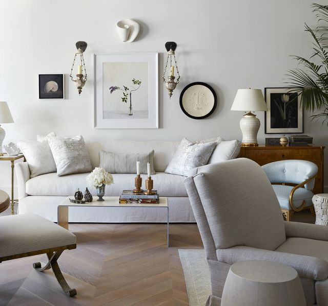 a pair of 19th century italian sconces flanks a still life painting by alec soth that hangs above a white sofa