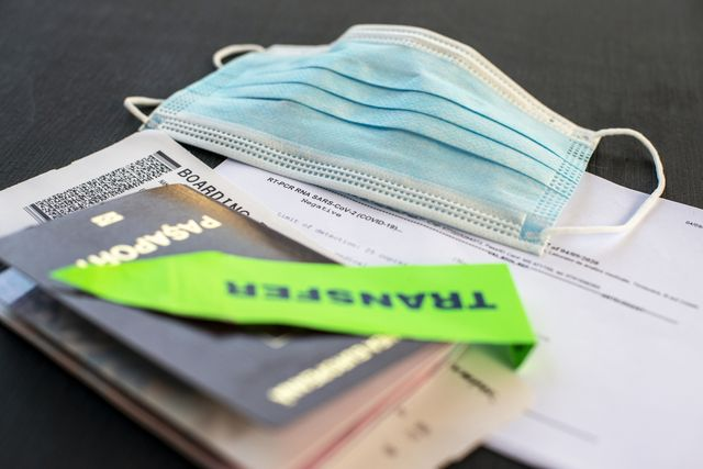 passport, face mask, boarding pass and covid pcr test  at the airport check in desk